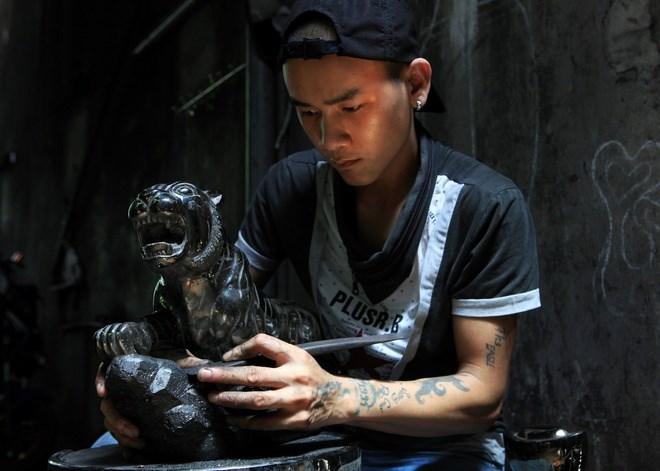 Coal carving craftsman Nguyen Van Xuan, who has six years of experience, is carving a tiger from coal. Photo credit: VnExpress