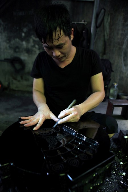 Nguyen Tuan Quyet, who runs the shop, and a coal-carved handiwork