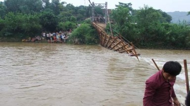 Suspension bridge breaks, dozens of people fall into flood water